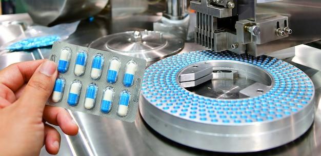 Ręka trzyma błękitną kapsuły paczkę przy medycyny pigułki linią produkcyjną, przemysłowy farmaceutyczny pojęcie.