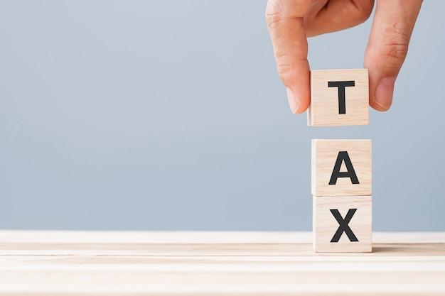 Ręka trzyma blok drewna kostki z tekstem podatku. koncepcja finansów, zarządzania, ekonomii, biznesu i czasu do opodatkowania
