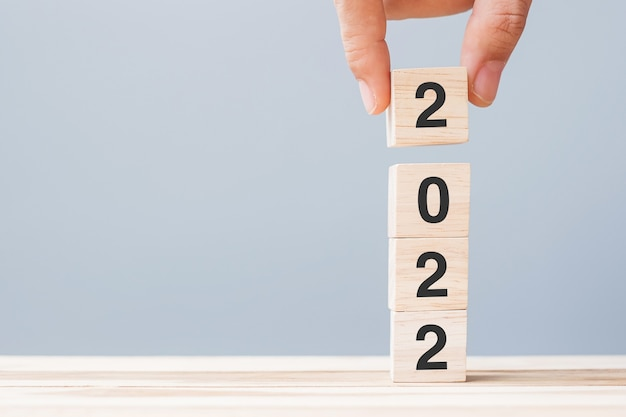 Ręka trzyma blok drewniany sześcian z tekstem 2022 na tle tabeli. koncepcje rozwiązania, planu, przeglądu, celu, rozpoczęcia i świąt noworocznych
