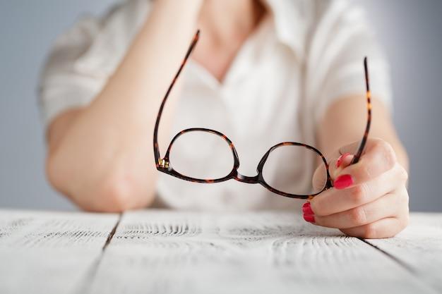 Ręka trzyma brązowe oprawione okulary