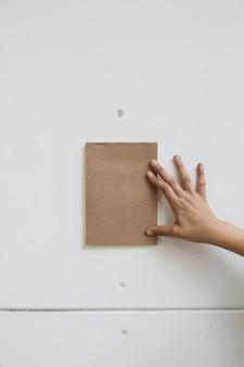 Ręka trzyma brązowy notatnik na białej ścianie