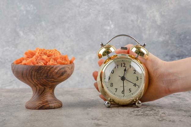 Ręka trzyma budzik i miskę makaronu na marmurowym tle