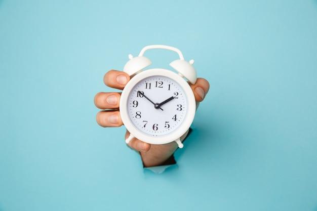Ręka trzyma budzik przez niebieski otwór papieru. zarządzanie czasem i koncepcja terminów.