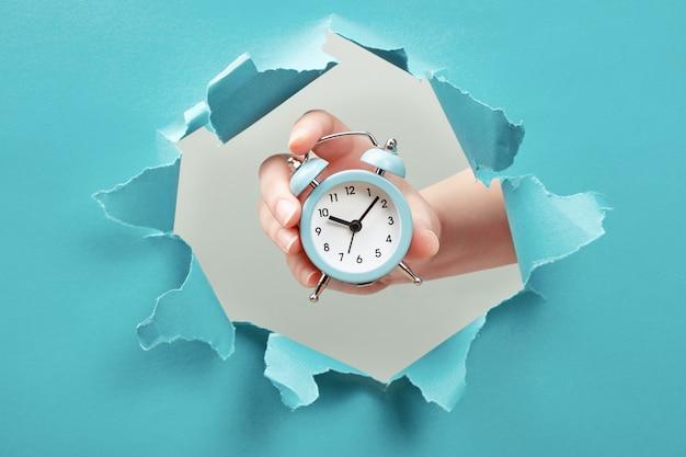 Ręka trzyma budzik przez otwór papieru. koncepcja zarządzania czasem i terminem