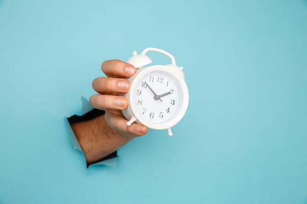 Ręka trzyma budzik przez otwór papieru. zarządzanie czasem i koncepcja terminów.