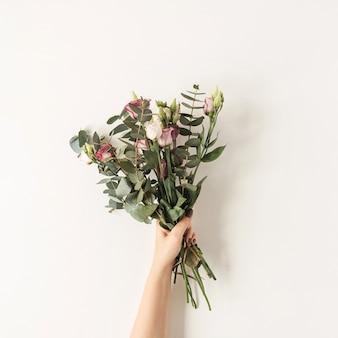 Ręka trzyma bukiet kwiatów kolorowych róż przed białą ścianą