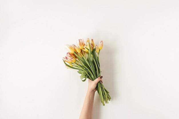 Ręka trzyma bukiet kwiatów kolorowych tulipanów na białej ścianie.