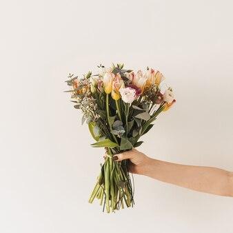 Ręka trzyma bukiet kwiatów tulipanów na białej ścianie