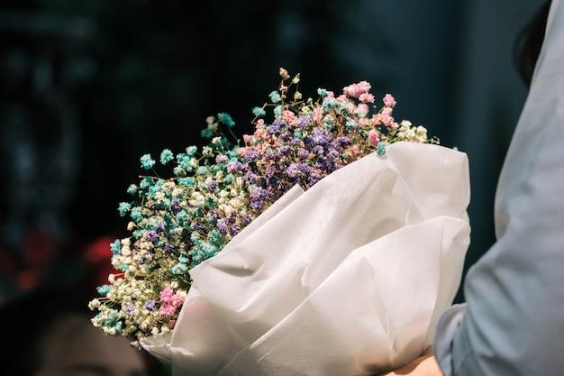 Ręka trzyma bukiet suszonych kwiatów łyszczec zawinięte w papier
