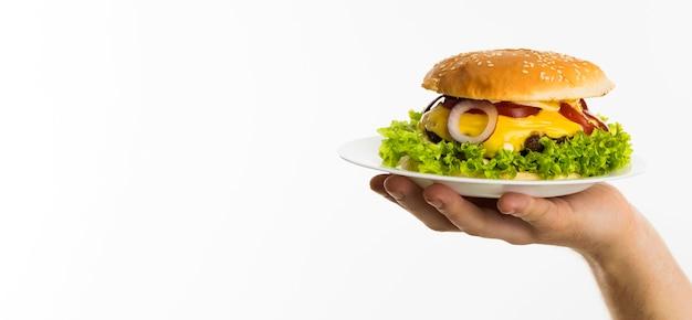 Ręka trzyma burgera na talerzu z miejsca na kopię