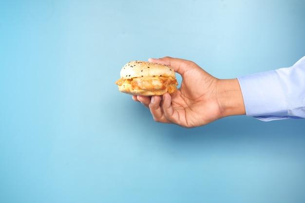 Ręka trzyma burgera wołowego przed niebieskim backgrund z miejsca na kopię