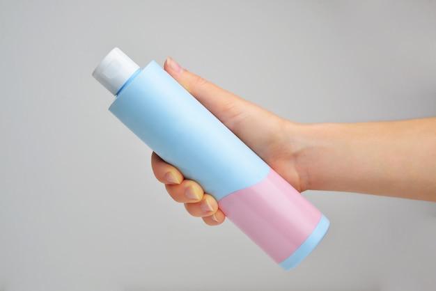 Ręka trzyma butelkę szamponu na białym tle