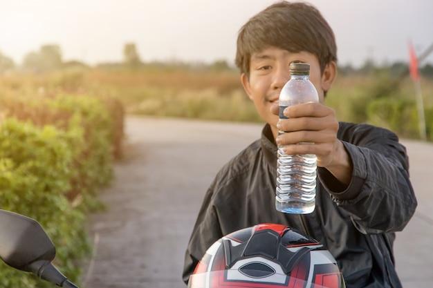 Ręka trzyma butelkę wody z dużym rowerem, letnie wakacje na świeżym powietrzu i widok wieczorem