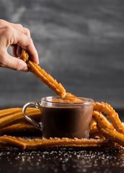 Ręka trzyma churros nad szklanką czekolady