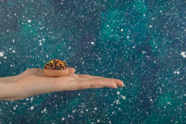 Ręka trzyma ciastko na kolorowej powierzchni.