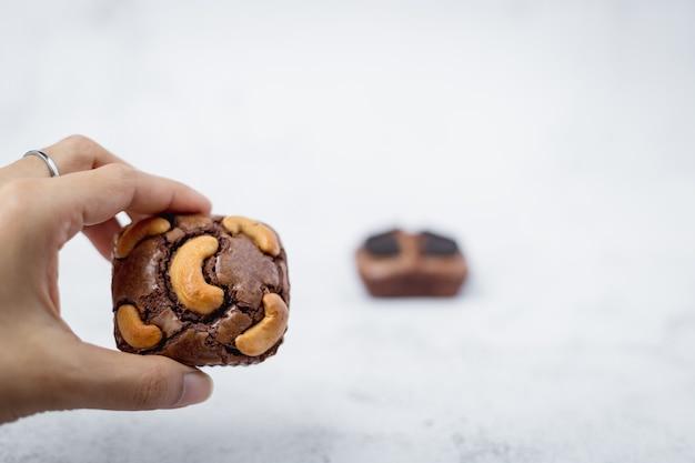 Ręka trzyma ciasto brownie na białym tle dla piekarni, żywności i koncepcji jedzenia