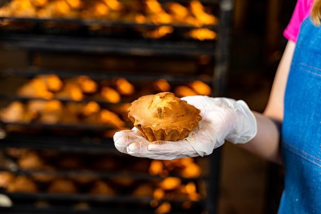 Ręka trzyma ciasto lub muffin. tło fabryki piekarnika.