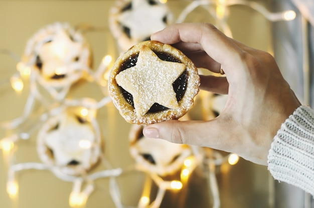 Ręka trzyma ciasto mielone, tradycyjny świąteczny deser