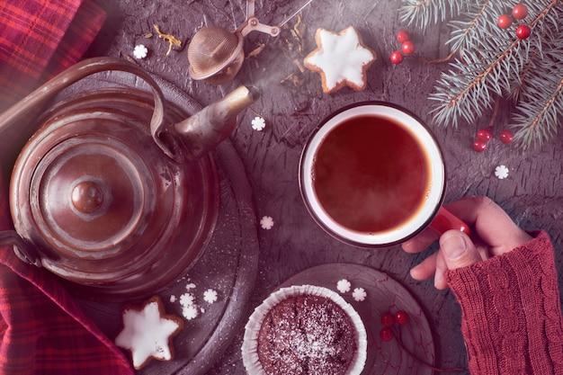 Ręka trzyma ciepłą filiżankę herbaty w zimny poranek jesienią