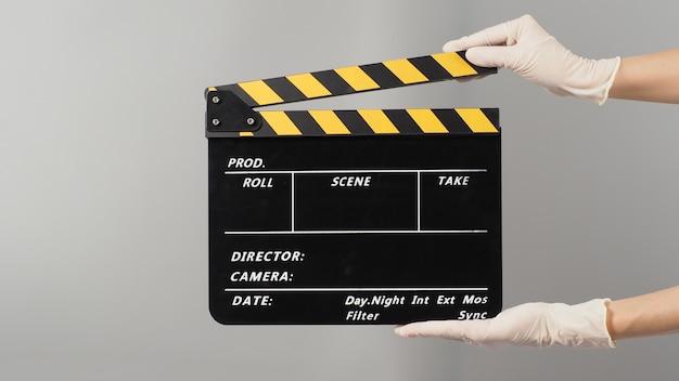 Ręka trzyma czarną deskę klapy i nosi rękawicę medyczną. jest używany w produkcji wideo i przemyśle filmowym na szarym tle.