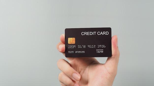 Ręka trzyma czarną kartę kredytową na białym tle na szarym tle.