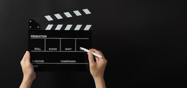 Ręka trzyma czarną tablicę klapy lub tabliczkę filmową i pisak na czarnym tle