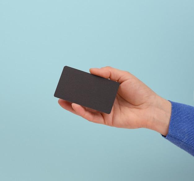 Ręka trzyma czarną wizytówkę, niebieskie tło, z bliska