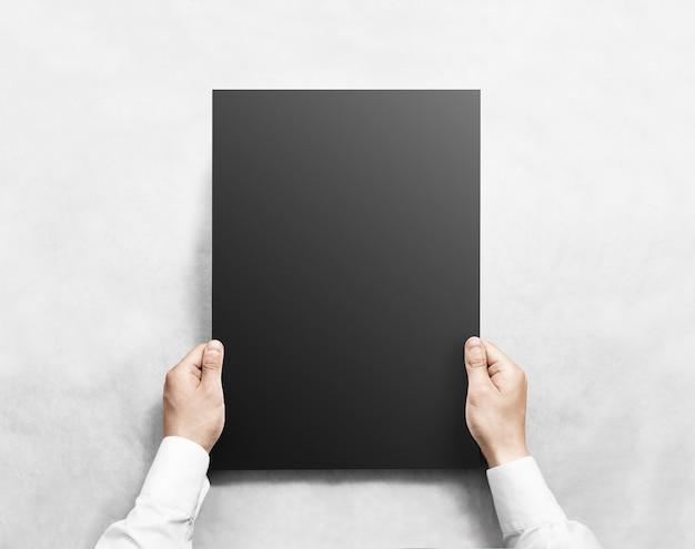 Ręka trzyma czarny pusty plakat, na białym tle.