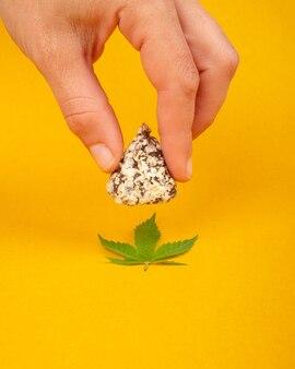 Ręka trzyma czekoladki z konopi, rekreacyjne używanie marihuany.