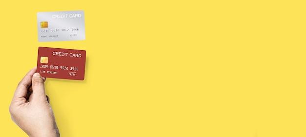 Ręka trzyma czerwoną kartę kredytową i srebrną kartę kredytową na górze, izolowany na żółtym tle i ścieżkę przycinającą.