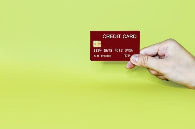 Ręka trzyma czerwoną kartę kredytową na żółtym tle, karta kredytowa może służyć do płacenia za towary lub usługi, koncepcja karty kredytowej. ścieżka przycinająca karty kredytowej.