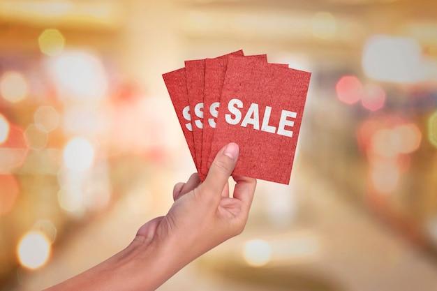 Ręka trzyma czerwoną kartkę z tekstem sprzedaż