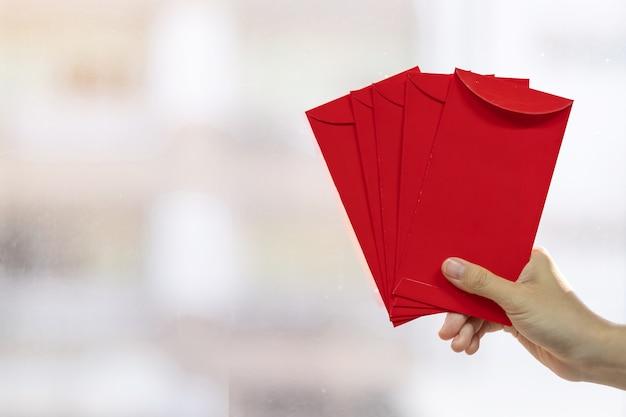 Ręka trzyma czerwoną kopertę lub ang pao. koncepcja obchodów chińskiego księżycowego nowego roku