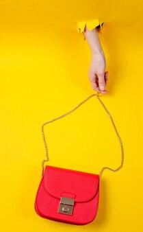 Ręka trzyma czerwoną skórzaną torbę na łańcuchu przez rozdarty żółty papier. minimalistyczna koncepcja mody