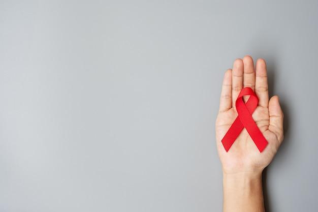 Ręka trzyma czerwoną wstążkę na światowy dzień pomocy