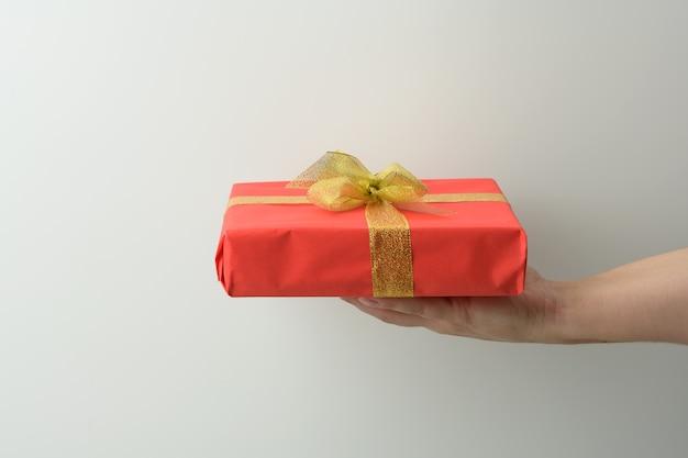 Ręka trzyma czerwone pudełko na szarym tle, koncepcja wszystkiego najlepszego