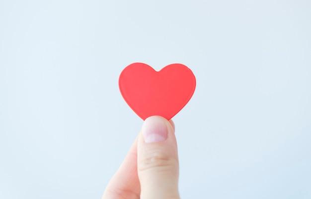 Ręka trzyma czerwone serce. dawstwo narządów, ubezpieczenie rodzinne. światowy dzień serca, światowy dzień zdrowia, wdzięczność, bądź miły, bądź wdzięczny. koncepcja miłości.