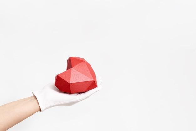 Ręka trzyma czerwone serce na białym tle. opieka healht, koncepcja miłości. obraz na światowy dzień zdrowia, światowy dzień serca.