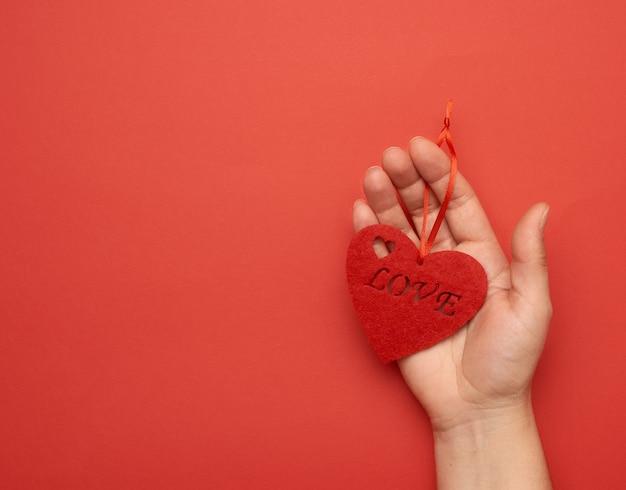 Ręka trzyma czerwone serce na czerwono