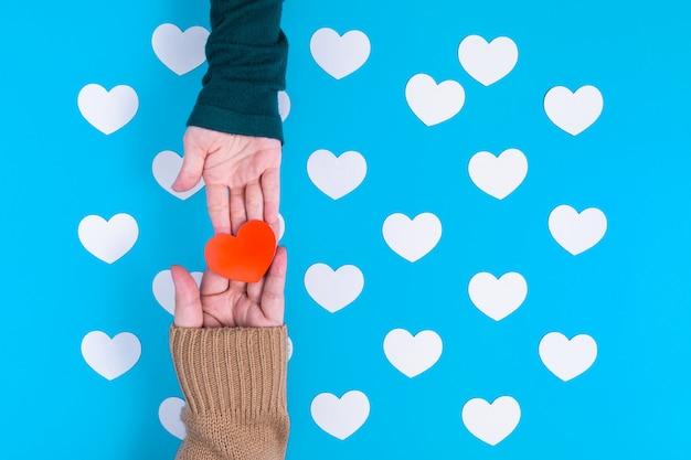 Ręka trzyma czerwone serce na czyjejś dłoni, te są nad grupą białych serc umieszczonych na niebiesko