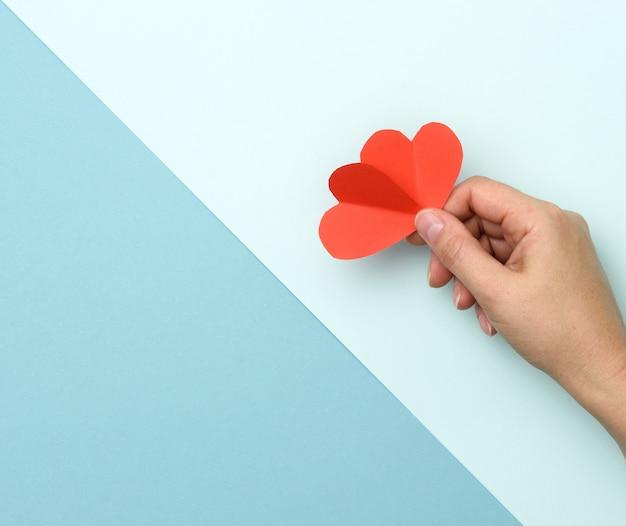 Ręka trzyma czerwone serce papieru