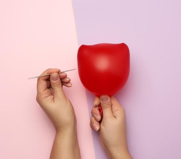 Ręka trzyma czerwony balon i ostrą metalową igłę