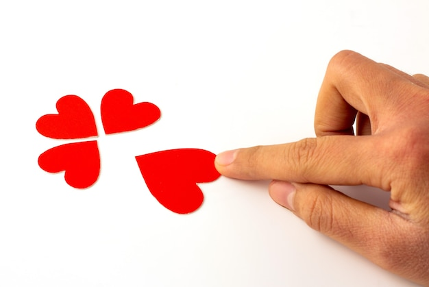 Ręka trzyma czerwony papier w kształcie serca na białym tle, koncepcja miłości i walentynki.