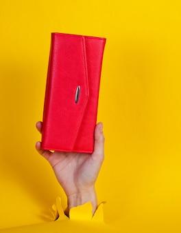 Ręka trzyma czerwony portfel przez rozdarty żółty papier. minimalistyczna koncepcja kreatywnej mody