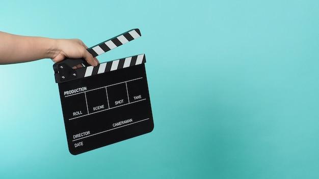 Ręka trzyma deskę klapy czarny lub łupek filmowy na zielonej mięty lub tiffany blue tle.