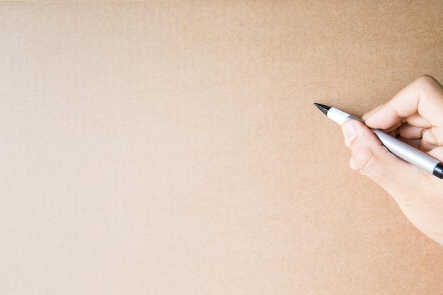 Ręka trzyma długopis z brązowym papierowym tłem