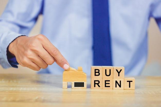 Ręka trzyma do domu z kup lub wynajem, koncepcja nieruchomości.