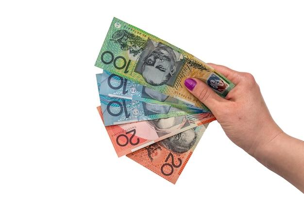 Ręka trzyma dolara australijskiego na białym tle