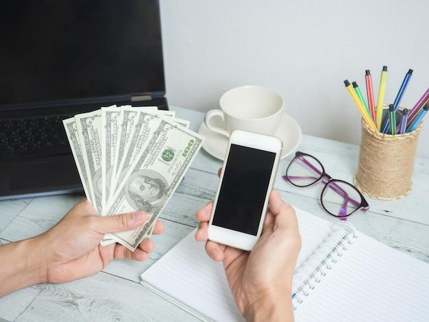 Ręka trzyma dolara pieniędzy i telefon komórkowy z obszarem roboczym na białym tle stołu z drewna