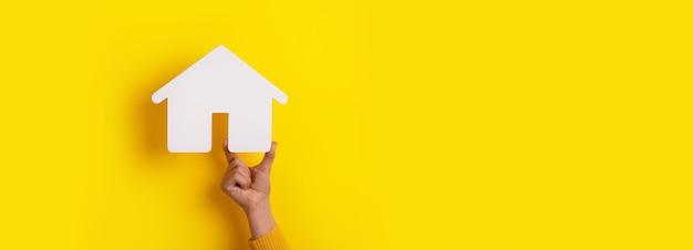 Ręka trzyma dom na żółtym tle, koncepcja inwestycji w nieruchomości, makieta panoramiczna